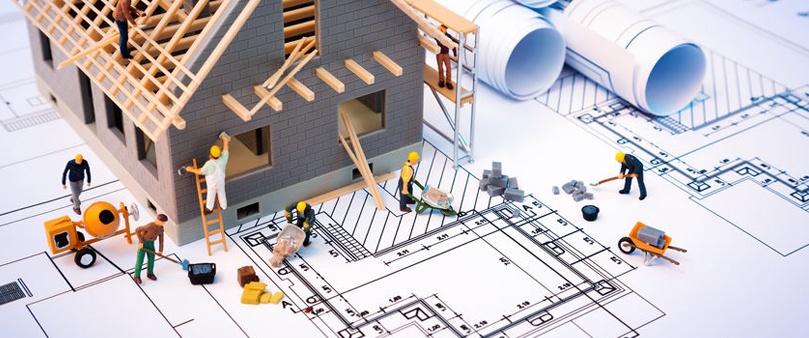 miniature figures building a house with planning documents
